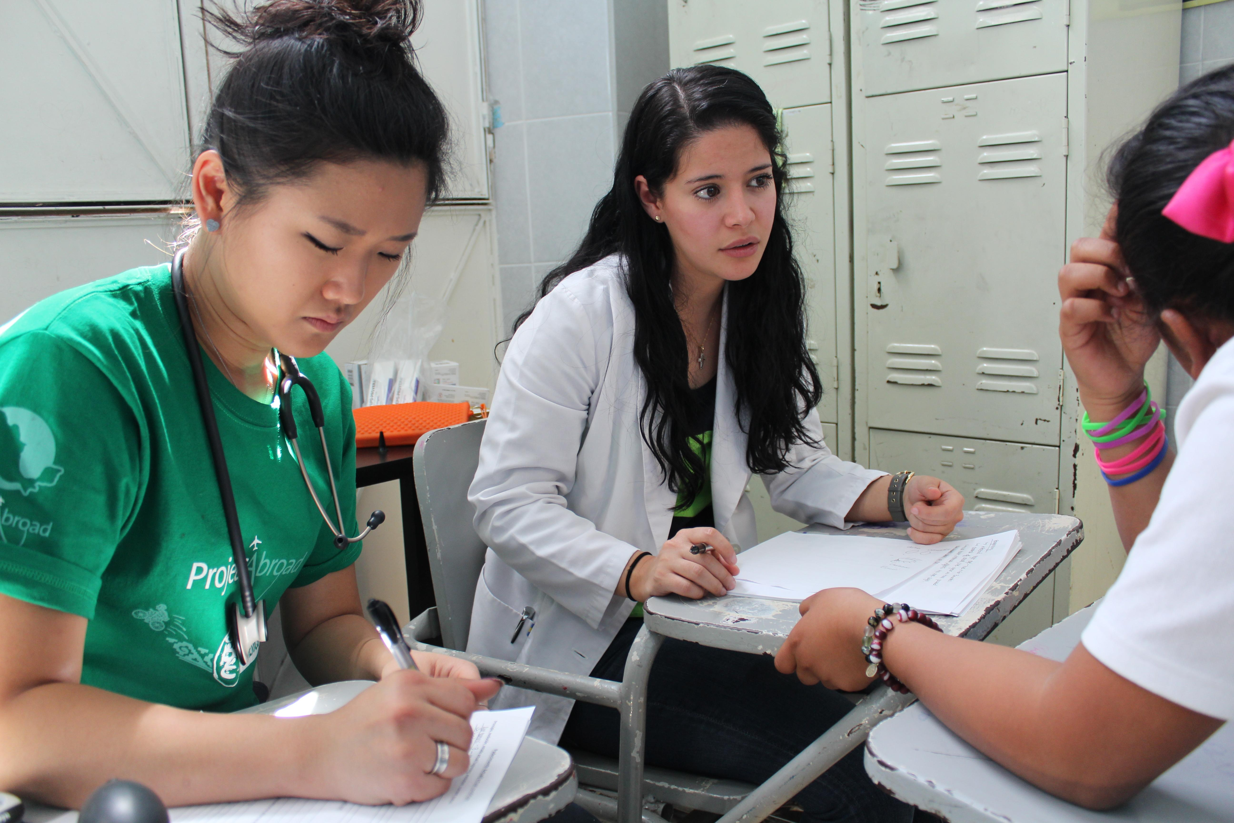 Female Medical Interns make notes on paper with a local doctor during their internship in Mexico.